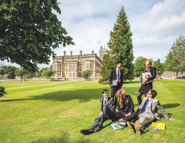 pupils sitting on lawns, Rendcomb main building in background, sunny day trees