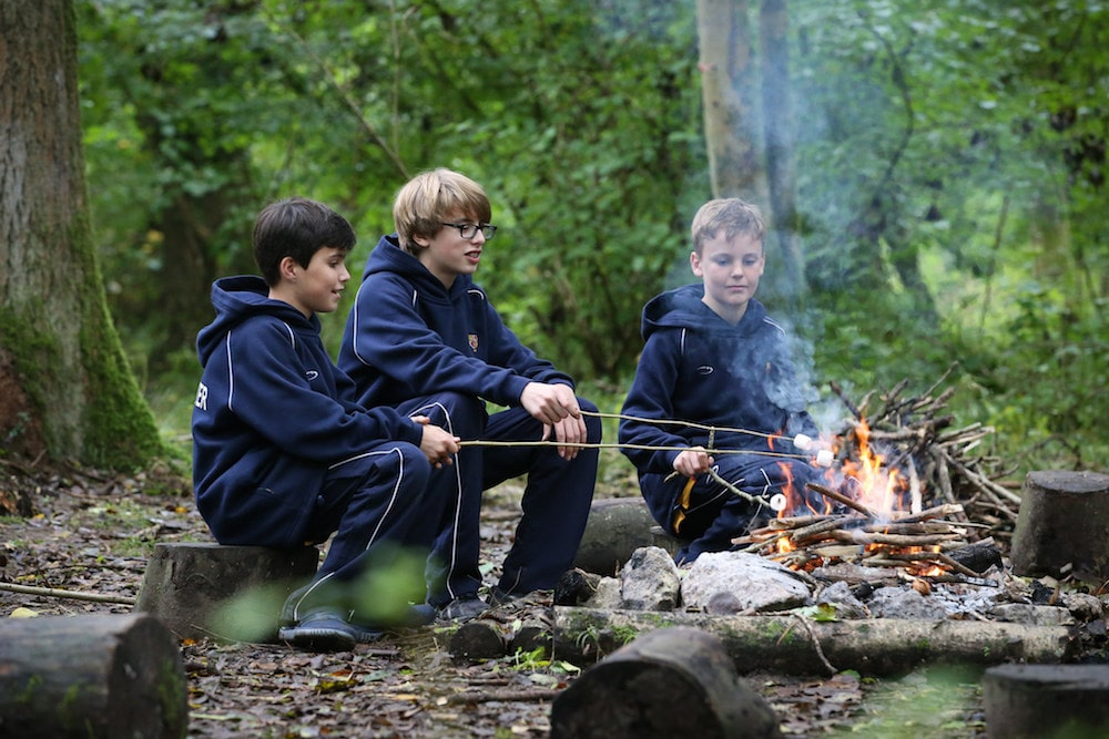 boys roasting marshmallows over an open fire in the woods