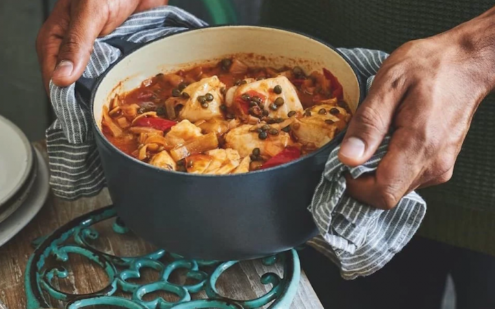 grey Le Creuset pot with fish stew