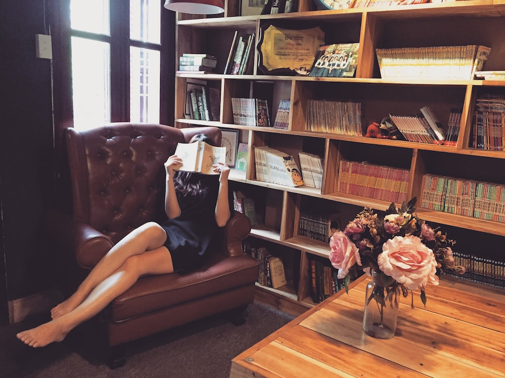 woman reading book leather armchair bookcase pink roses vase