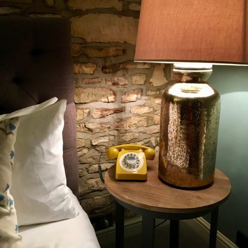yellow telephone bedside lamp orange lampshade bedside table bed