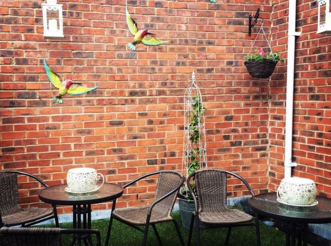 roof terrace brick wall tables and chairs hanging plant birds