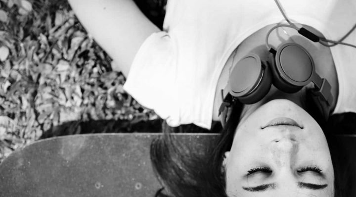 black and white woman lying on skateboard relaxing