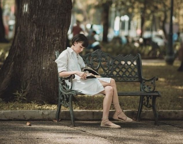 woman reading book on bench
