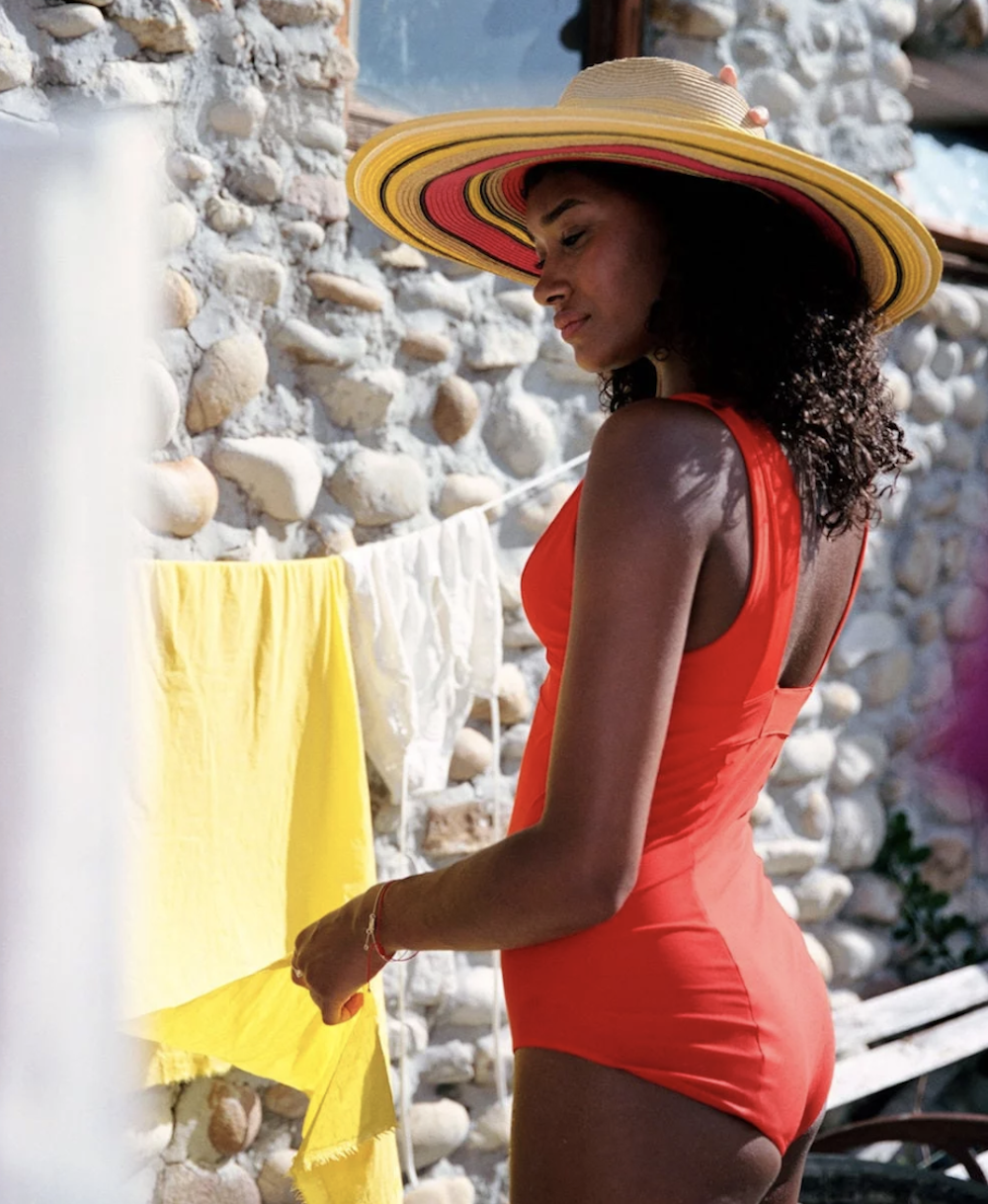 woman red swimsuit sunhat yellow towel